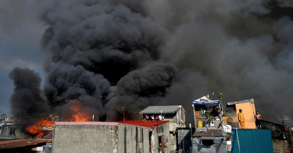 12.mar.2016 - Bombeiro e morador observam, do alto de um telhado, a incêndio de grande proporção avançando sobre área residencial de Manila (Filipinas). Quase 200 famílias foram atingidas pelas chamas, de acordo com a Agência de Proteção contra Incêndios das Filipinas