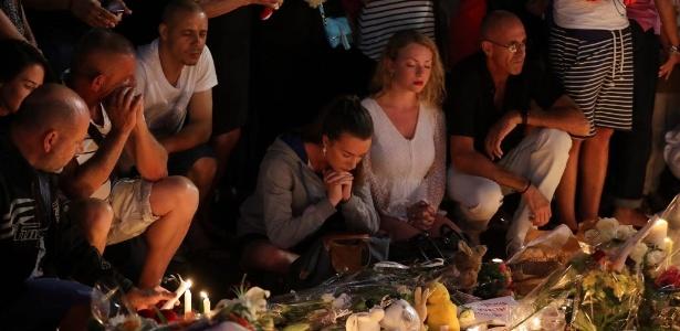 Pessoas rezam em torno de memorial improvisado para homenagear as vítimas do ataque com caminhão na cidade francesa de Nice - Valery Hache/ AFP
