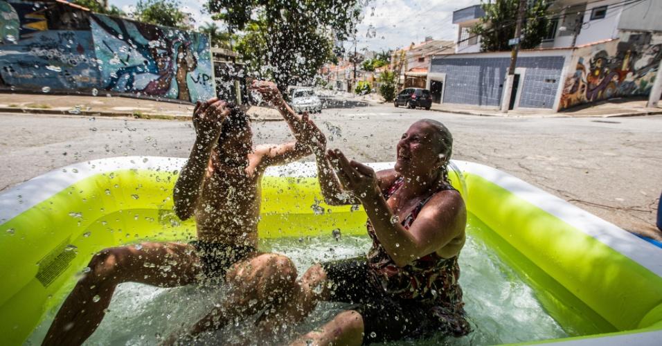 Um grupo de 30 pessoas, muitas vestidas em trajes de banho aproveitou o calor para tomar um banho no meio da rua
