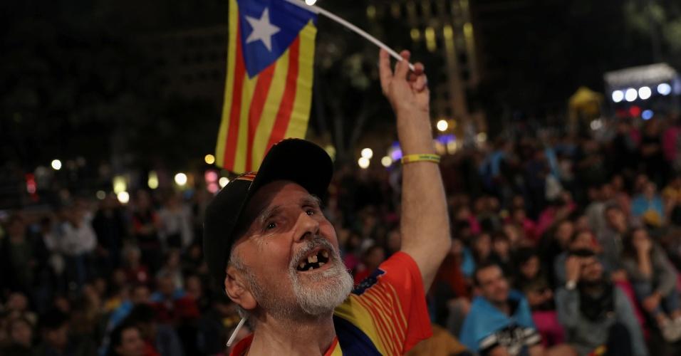 1º.out.2017 - Homem segura a bandeira separatista catalã em meio a manifestantes na Plaza Catalunya, em Barcelona, após o fim do referendo pela separação da região da Espanha