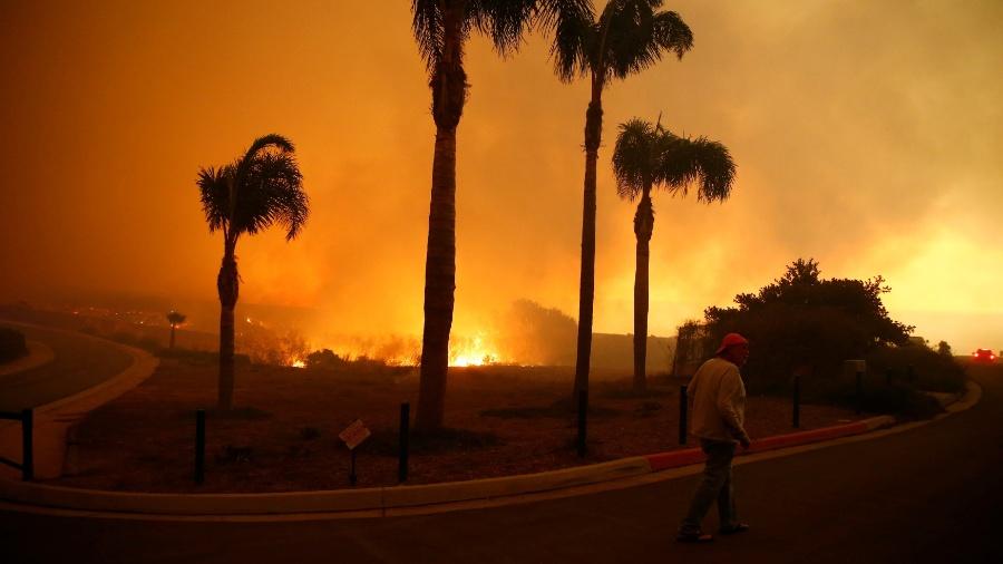 Homem caminha em bairro tomado pelas chamas na Califórnia - ERIC THAYER/REUTERS