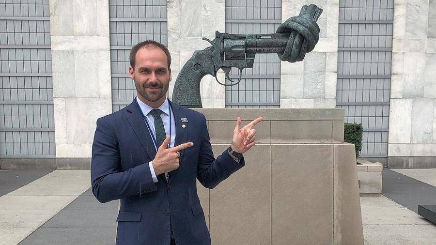 """Eduardo Bolsonaro posa fazendo """"arminha"""" em frente a escultura pela paz - Reprodução/Instagram"""