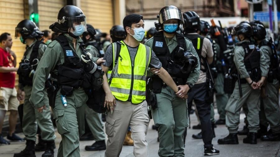 Policiais prendem homem (ao centro) durante protesto em Hong Kong contra a nova lei de segurança nacional imposta pela China  - Isaac Lawrence/AFP