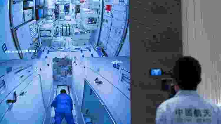 Membro da equipe grava vídeos da imagem da tela no Centro de Controle Aeroespacial de Pequim, em 17 de junho de 2021, mostrando os três astronautas chineses a bordo da Shenzhou-12 entrando no módulo central da estação espacial Tianhe - Xinhua/Jin Liwang - Xinhua/Jin Liwang