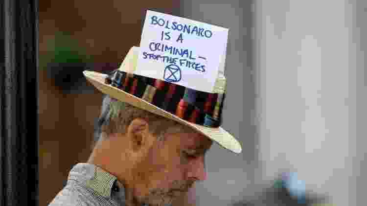 'Bolsonaro é um criminoso — Parem os incêndios', diz mensagem no chapéu de ativista em protesto na Embaixada do Brasil em Londres, em 2019 - Getty Images - Getty Images