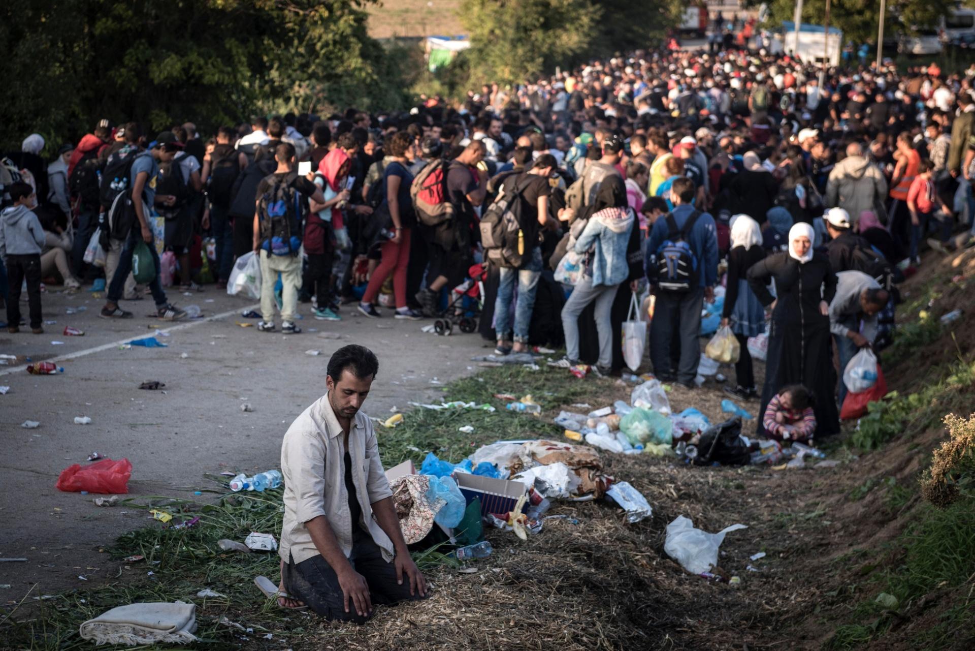 Homem reza enquanto espera com outros imigrantes para cruzar a fronteira entre a Sérvia e a Croácia