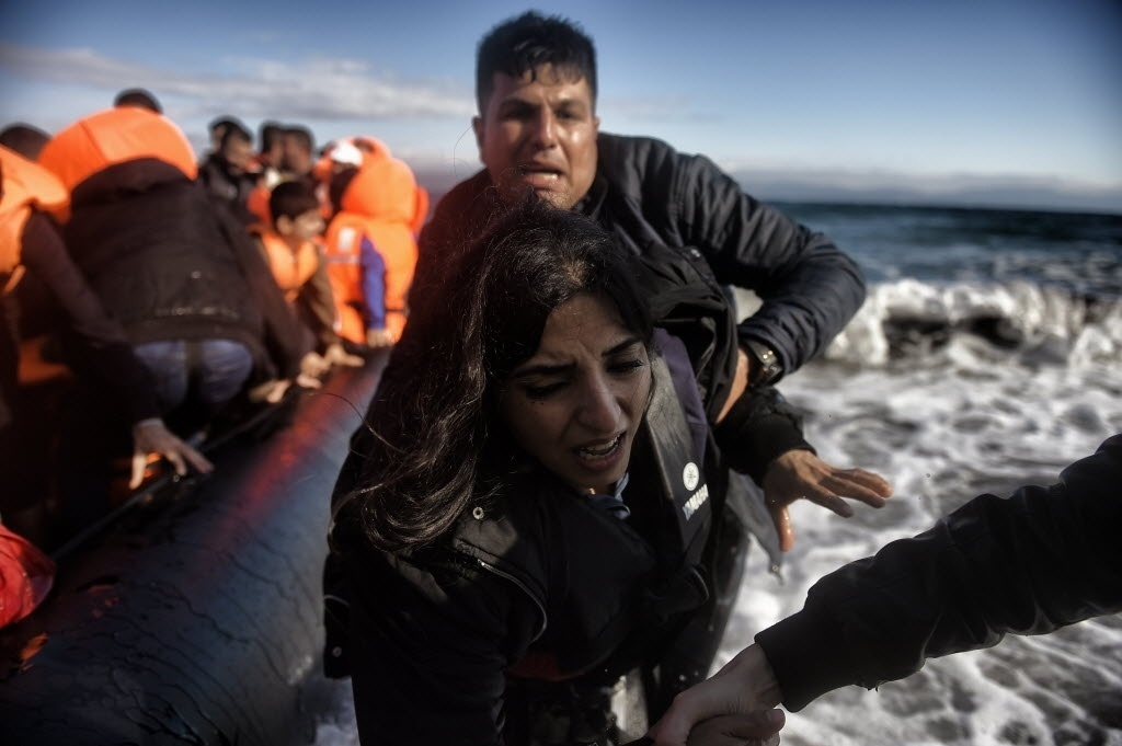 1º.out.2015 - Mulher recebe ajuda para sair de barco que chegou na ilha Lesbos, na Grécia, após sair da Turquia e atravessar o mar Egeu. As autoridades gregas evacuaram acampamento improvisado para migrantes no centro de Atenas e os levaram para instalações abandonadas dos Jogos Olímpicos de 2004, reabertas exclusivamente para abrigar os refugiados