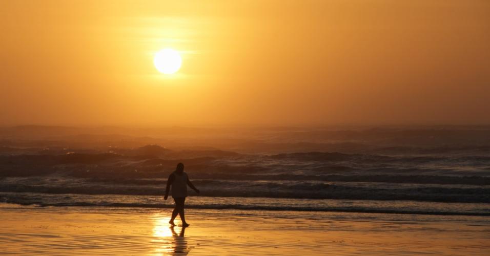"""5.jan.2016 - Banhista caminha pela praia Guilhermina, na cidade de Praia Grande, em São Paulo, durante o nascer do sol que """"pintou"""" o céu de amarelo"""