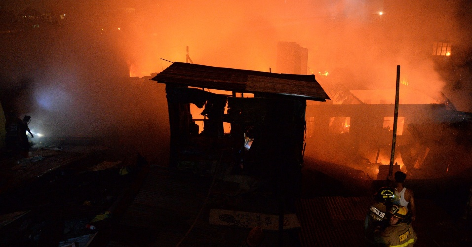 20.jan.2016 - Bombeiros e residentes tentam controlar fogo que consumiu várias casas em Manila, nas Filipinas. Incêndio atingiu conjunto de residências informais na área, mas ninguém ficou ferido, segundo relatos iniciais