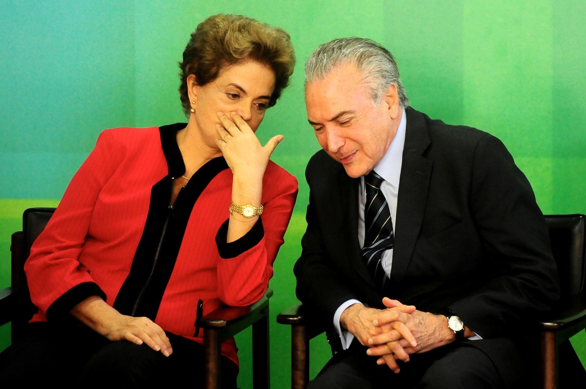 2.mar.2016 - A presidente Dilma Rousseff conversa com o seu vice, Michel Temer, durante solenidade de assinatura do acordo de compensações com a empresa Samarco devido ao acidente de Mariana (MG) no Palácio do Planalto, em Brasília