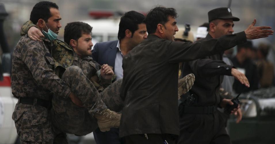 19.abr.2016 - Agente de segurança ferido é socorrido por colegas depois de um atentado suicida no centro de Cabul, perto do Ministério da Defesa do Afeganistão. O ataque, seguido de um tiroteio entre tropas afegãs e insurgentes, deixou um número ainda indeterminado de mortos e dezenas de feridos