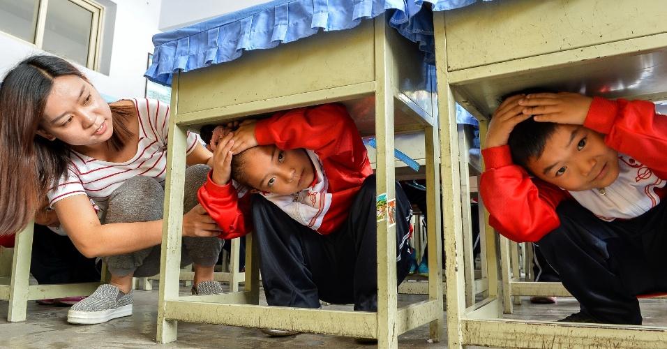 12.mai.2016 - Estudantes se protegem embaixo das carteiras durante treinamento para ação em caso de terremoto na cidade de Xingtai, no norte da China. O governo do país instituiu 12 de maio como o Dia da Prevenção de Desastres e Redução de Danos
