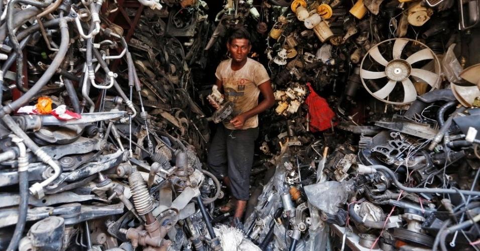 1º.jun.2016 - Mecânico carrega peça em loja de materiais automotivos usados em Mumbai, na Índia