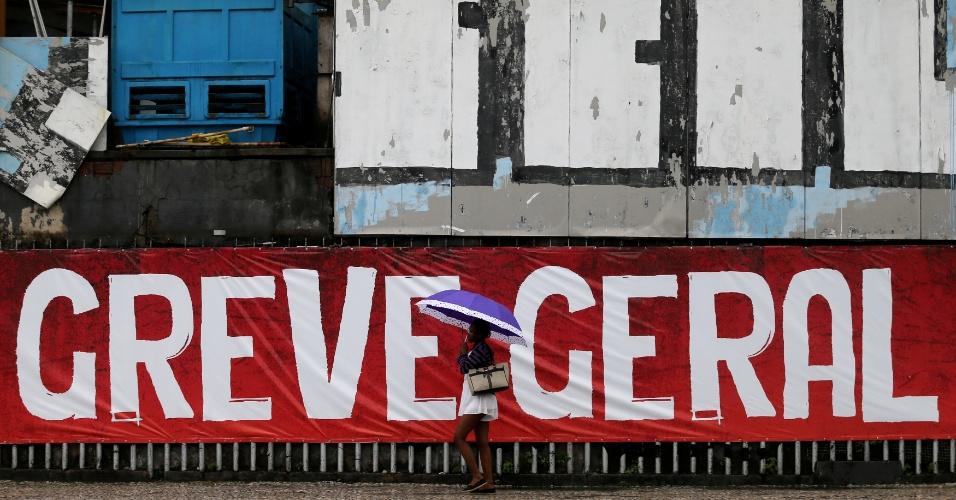 """28.abr.2017 - Mulher passa em frente a uma faixa com os dizeres """"greve geral"""", no Rio de Janeiro, nesta sexta. O dia de hoje é marcado por paralisações e protestos contra as reformas trabalhista e da Previdência, propostas pelo governo Temer (PMDB)"""