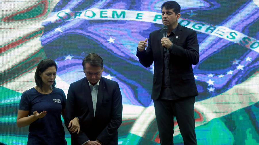 O presidente da República, Jair Bolsonaro, recebe oração de joelhos dobrados ao lado da mulher, Michelle Bolsonaro, e do pastor Josué Valandro Jr. na Igreja Batista Atitude, na Barra da Tijuca, zona oeste do Rio - WILTON JUNIOR/ESTADÃO CONTEÚDO