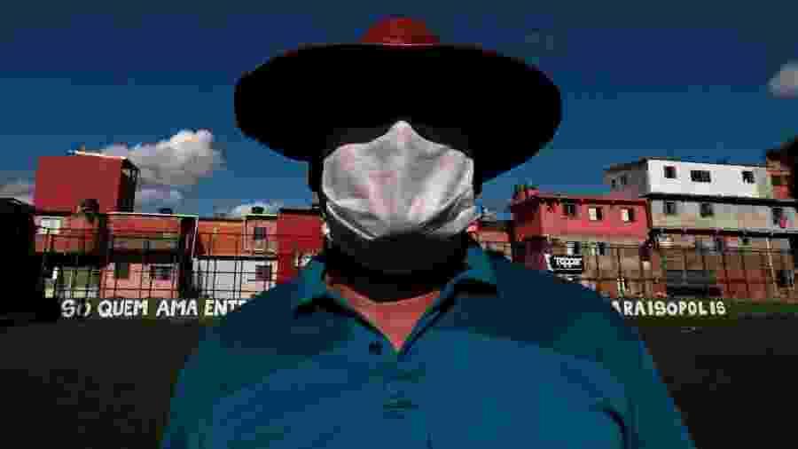 Homem voluntário usa máscara contra coronavírus em Paraisópolis (São Paulo) - Rodrigo Paiva/Getty Images