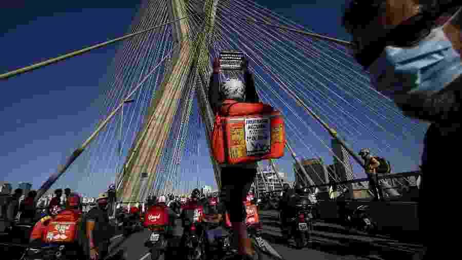 Entregadores de aplicativos se reúnem na Ponte Octávio Frias de Oliveira, a Ponte Estaiada, zona sul de São Paulo, e interrompem o trânsito para protestar contra a precarização do trabalho e reivindicar reajuste no valor, fim de bloqueios, entregas de EPI, entre outras demandas. Categoria faz paralisação nacional com exigências a apps como iFood, Rappi, Uber Eats e Loggi, nesta quarta-feira (01) - Newton Menezes/ Futura Press/ Estadão Conteúdo