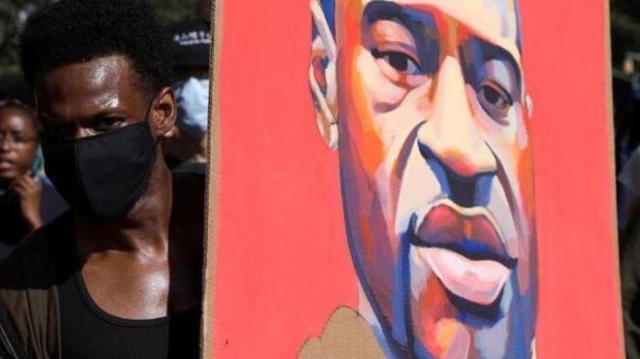Manifestante segura cartaz com rosto de George Floyd durante protesto em Nova York - CAITLIN OCHS