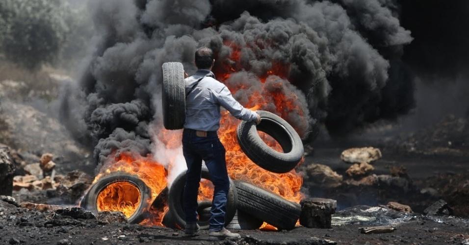 19.jun.2015 - Manifestante palestino joga pneus em barricada durante confronto com as forças de segurança de Israel, na Cisjordânia, nesta segunda-feira (19). O confronto começou após uma manifestação contra a desapropriação de terras palestinas na aldeia de Kfar Qaddum