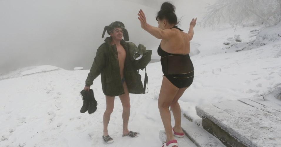 """6.jan.2015 - Mikhail Shakov (esq.), 23, que recentemente deixou o Exército e agora integra o clube Cryophile de nadadores de inverno, saúda outro integrante do grupo nas margens do rio Yenisei, na Rússia. A temperatura no momento era de -27°C. Para Shakov, nadar no frio é uma forma de se desconectar da rotina estressante. """"Todos os problemas saem de mim"""", diz"""