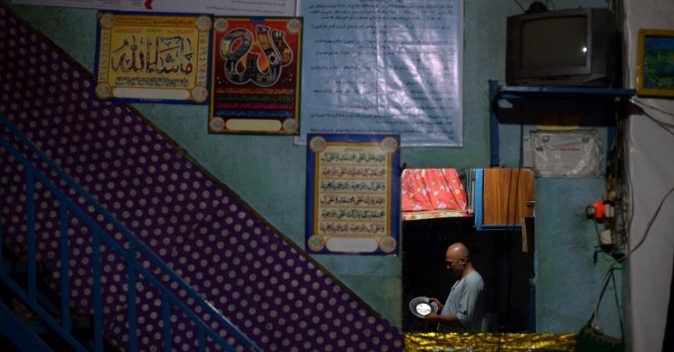 30.jul.2016 - Cozinheiro afegão lava pratos em seu restaurante na cidade de Mazar-i-Sharif, no Afeganistão