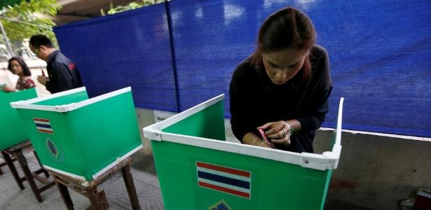 Mulher monta cabine para votação no referendo sobre nova Constituição da Tailândia