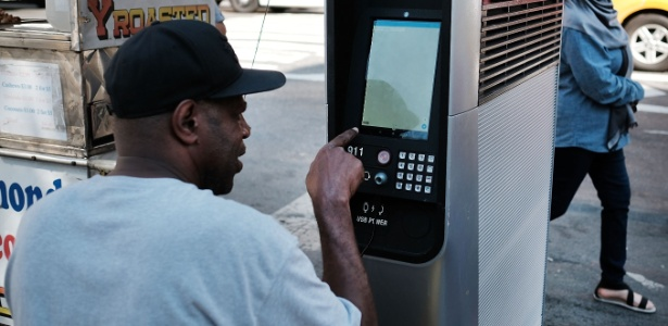 Sem teto usa um terminal LinkNYC em Nova York, EUA; quiosques Wi-Fi oferecem navegação na web de graça, chamadas telefônicas e uma estação de carregamento de celular