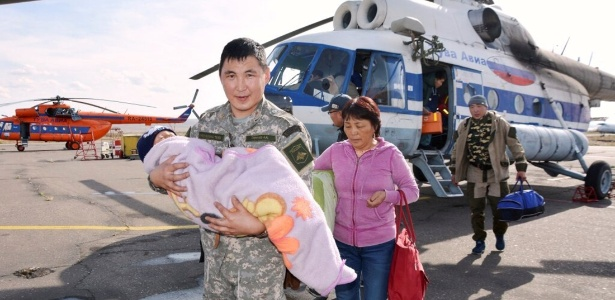 Foto divulgada pela Ministério de Emergências mostra integrante da equipe de resgate carregando o garoto Tserin, de 3 anos de idade, após ser resgatado na Sibéria