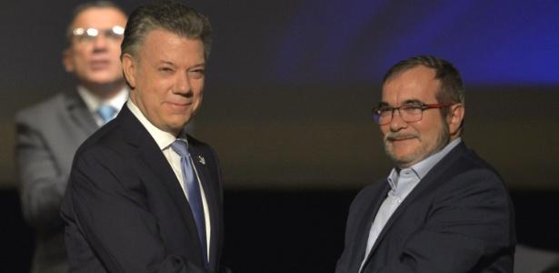 O presidente da Colômbia, Juan Manuel Santos (esq) e o líder das Farc, Timoleón Jimenez, apertam as mãos após assinarem o segundo acordo de paz, em Bogotá