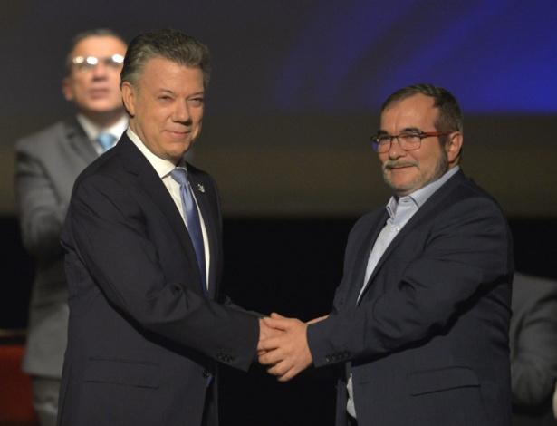 O presidente da Colômbia, Juan Manuel Santos (esq) e o líder das Farc, Timoleón Jimenez, apertam as mãos após assinarem o segundo acordo de paz, em Bogotá - Luis Robayo/AFP