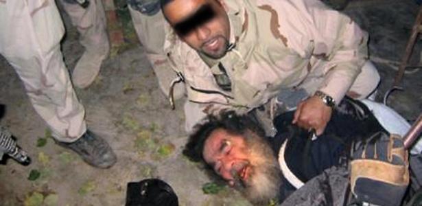 Foto mostra o ditador iraquiano Saddam Hussein sendo retirado do esconderijo próximo a Tikrit, no norte do Iraque