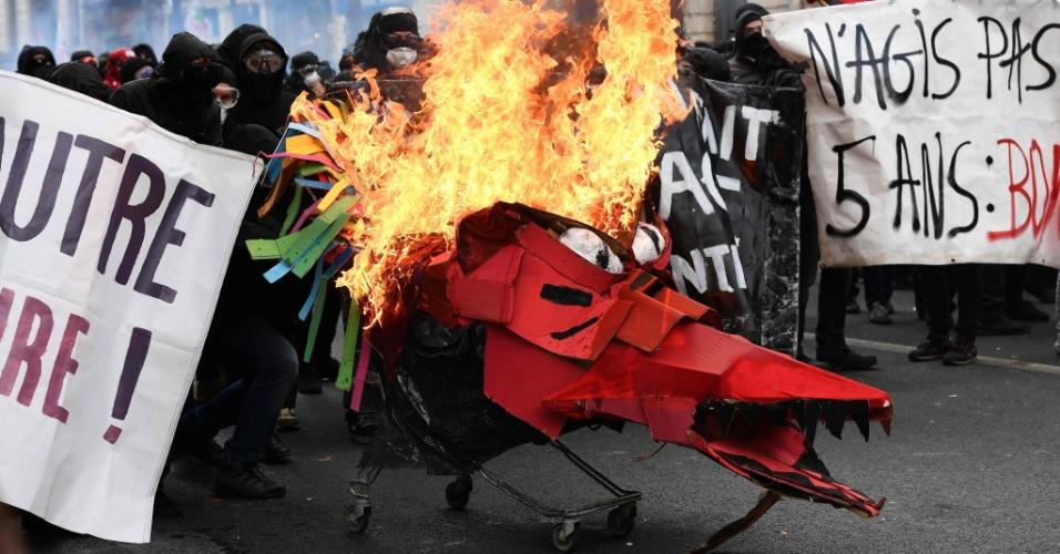 Manifestantes empurram carrinho em chamas contra policiais durante protestos no dia 1º de Maio em Paris