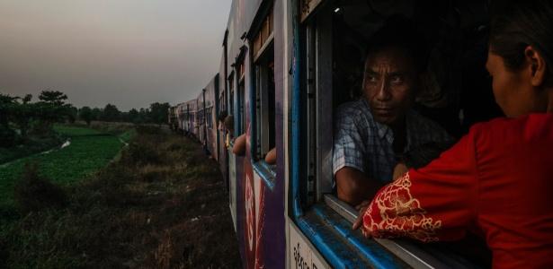 Passageiro observa a paisagem enquanto anda no trem em Yangon, em Mianmar