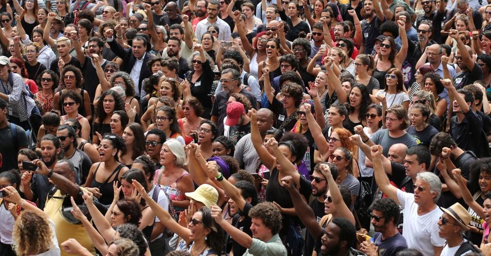 """15.mar.2018 - Manifestantes erguem os punhos e gritam """"Marielle vive! Presente"""" durante a chegada dos caixões com os corpos da vereadora Marielle Franco (PSOL-RJ) e do motorista dela Anderson Pedro Gomes à Câmara Municipal do Rio de Janeiro, no centro da capital fluminense, onde serão velados. O ato foi marcado por protestos por justiça"""