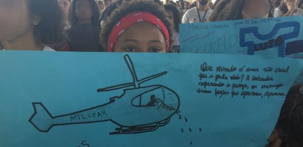 27.jun.2018 - Aluna segura cartaz com crítica a uso de helicóptero policial na Maré - UOL
