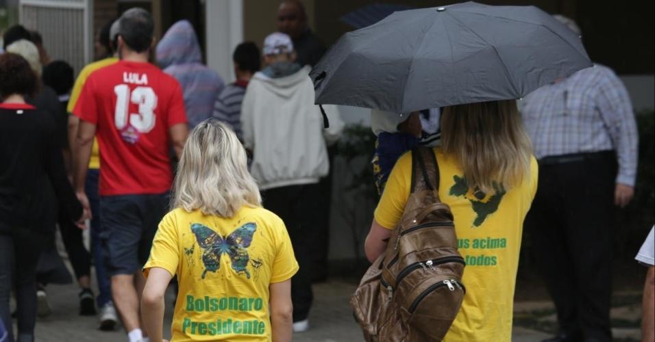 Eleitores usam a camisa do candidato Jair Bolsonaro (PSL) e do PT para votar no Mackenzie em Higienópolis