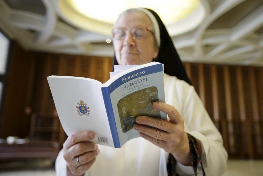 18.jun.2015 - Uma freira lê a nova encíclica publicada nesta quinta-feira (18), no Vaticano. No documento, o papa Francisco cobrou uma ação rápida para salvar o planeta da ruína ambiental, fazendo um apelo aos líderes mundiais para ouvirem