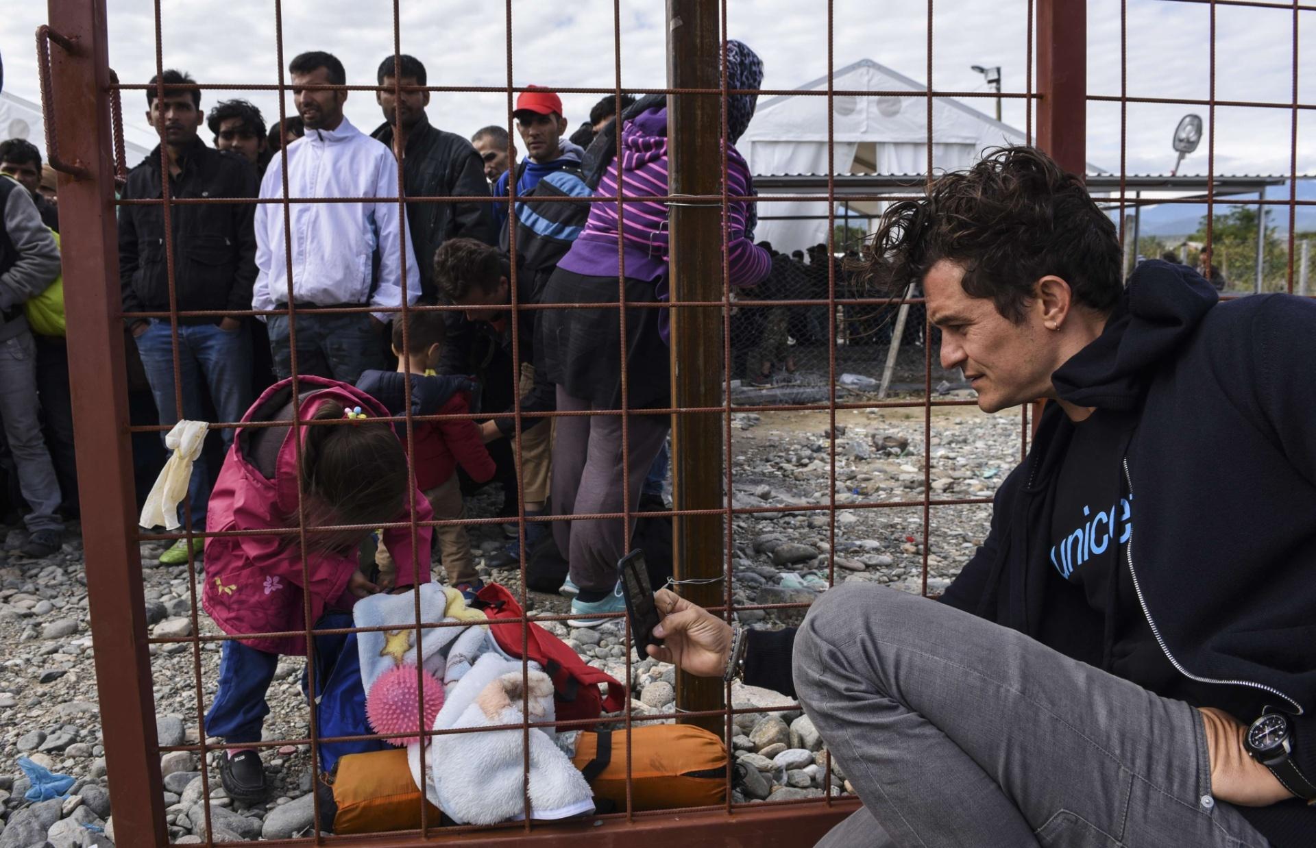 28.set.2015 - O ator britânico Orlando Bloom, embaixador da Boa Vontade do Unicef, fotografa criança em visita a campo de refugiados em Gevgelija, Macedônia