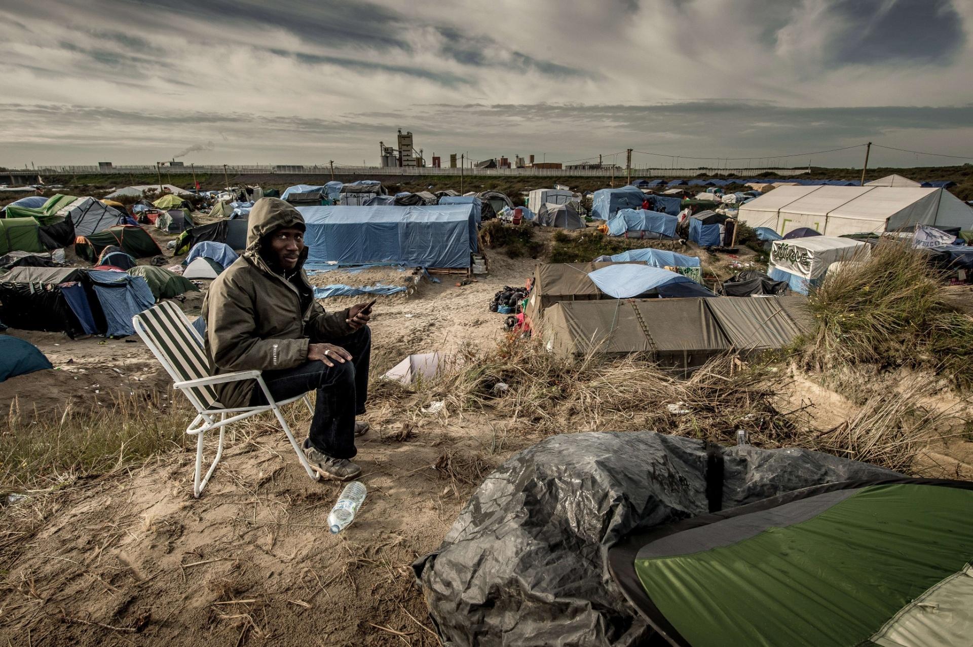 6.nov.2015 - Homem usa um celular para ligar para sua família no Sudão. Ele vive no acampamento criado para imigrantes africanos em Calais, na França. Um tribunal francês ordenou que o governo melhore as condições no local, após ONGs denunciarem