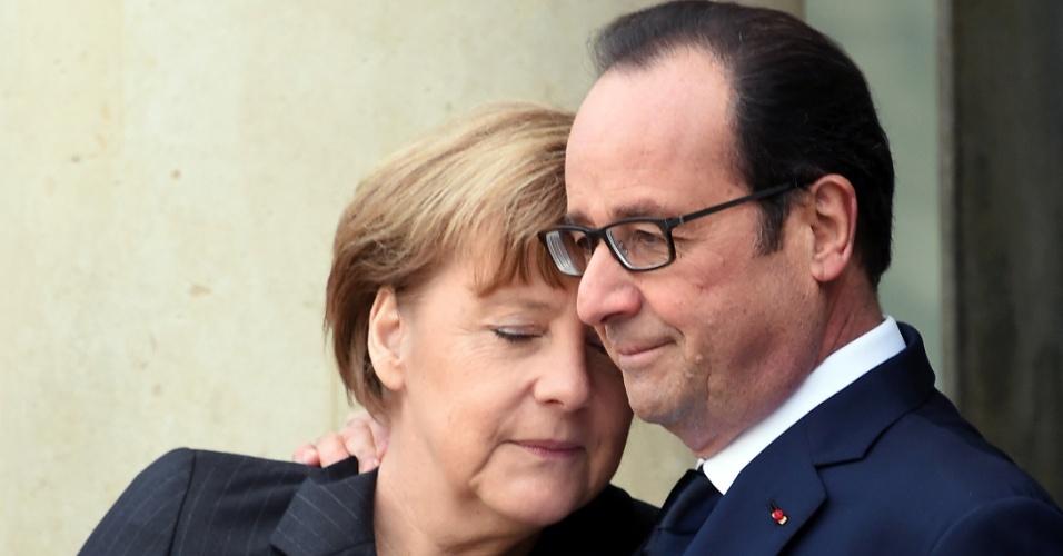 """11.jan.2015 - Presidente francês, François Hollande congratula-se com a chanceler alemã, Angela Merkel no Palácio do Eliseu antes de participar do comício União """"Marche Republicaine"""", em homenagem às 17 vítimas dos atentados terroristas em Paris, iniciados pela invasão do jornal satírico Charlie Hebdo, na França"""
