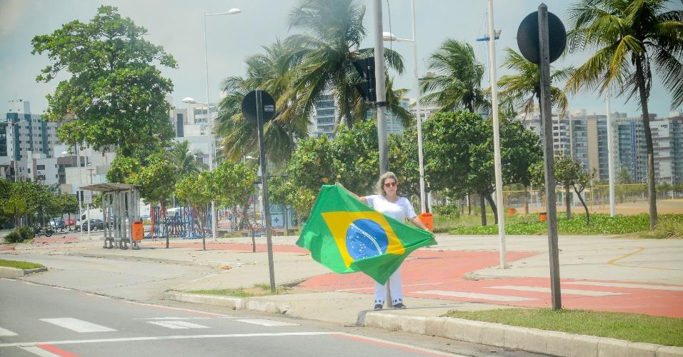 9.fev.2017 - Mulher protesta na orla da praia de Camburi, em Vitória, acenando a bandeira do Brasil