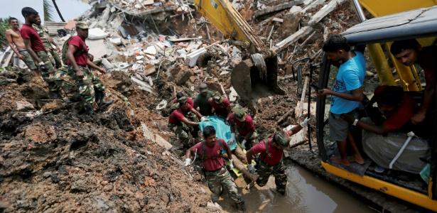 Militares carregam corpo de vítima de deslizamento em aterro sanitário em Colombo (Sri Lanka)