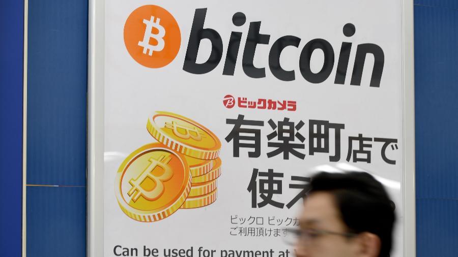 Homem passa por cartaz anunciando que bitcoin é aceito como forma de pagamento em loja de Tóquio, no Japão - Toru Yamanaka/AFP