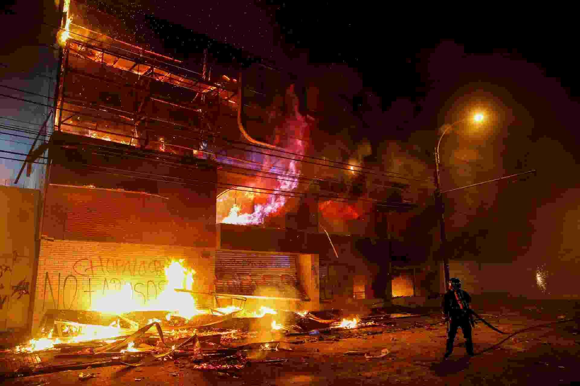 Bombeiro tenta combater as chamas em supermercado em Valparaíso, no Chile, durante onda de protestos contra o governo - Rodrigo Garrido/Reuters
