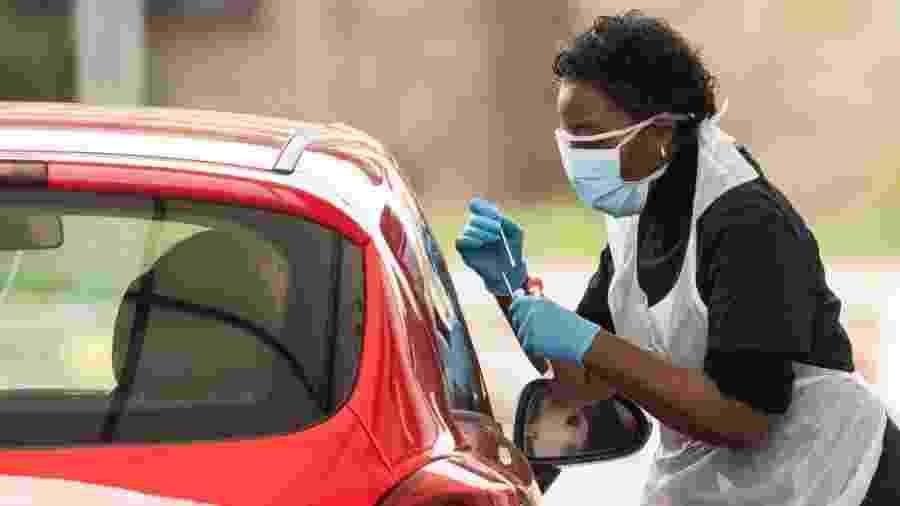 30.mar.2020 - De avental de plástico, enfermeira colhe amostra para teste de coronavírus em Chessington, no Reino Unido  - Dan Kitwood/Getty Images