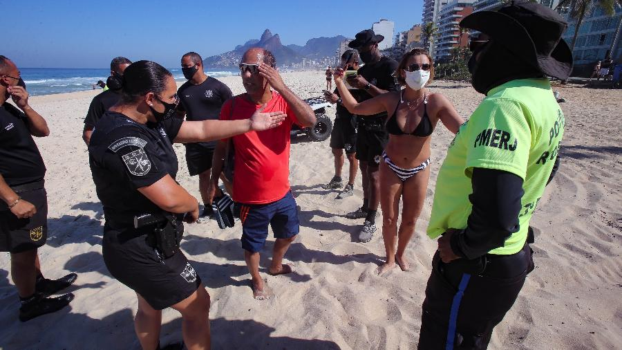 Policiais conversam com um casal que foi multado na praia de Ipanema, zona sul do Rio, ontem, por desobedecerem a determinação de não permanecer na areia - Wilton Junior/ Estadão Conteúdo