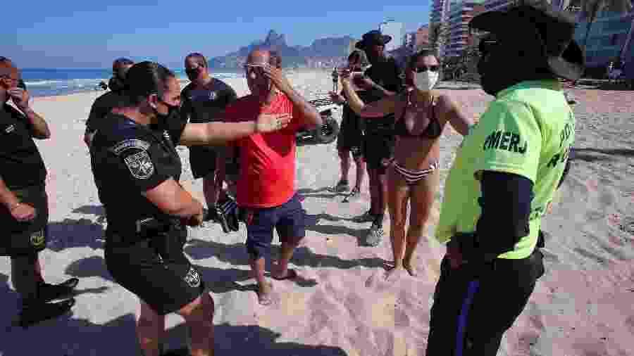Policiais conversam com um casal que foi multado na praia de Ipanema, zona sul do Rio, por desobedecerem a detemrinação de não permanecer na areia - Wilton Junior/ Estadão Conteúdo