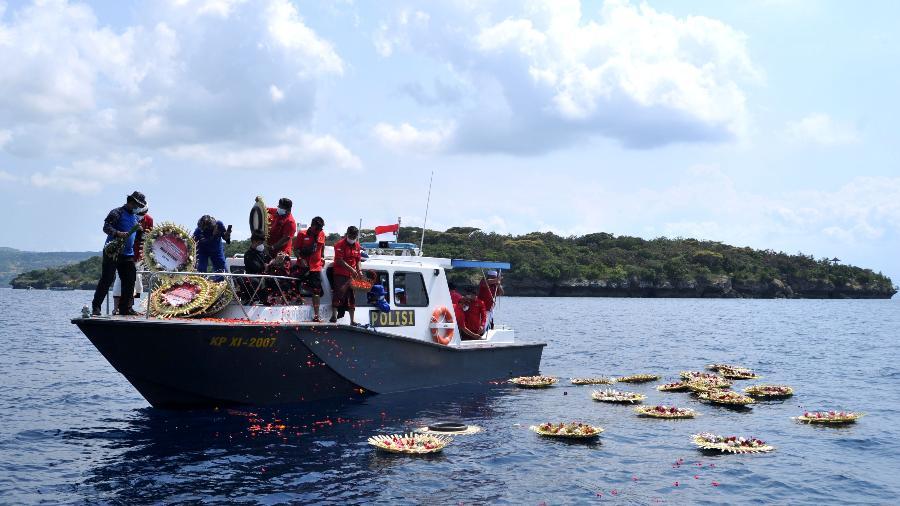 26.abr.2021-  Pessoas jogam pétalas de flores com nomes dos marinheiros que morreram em submarino no litoral da Indonésia - Antara Foto/Fikri Yusuf/via Reuters