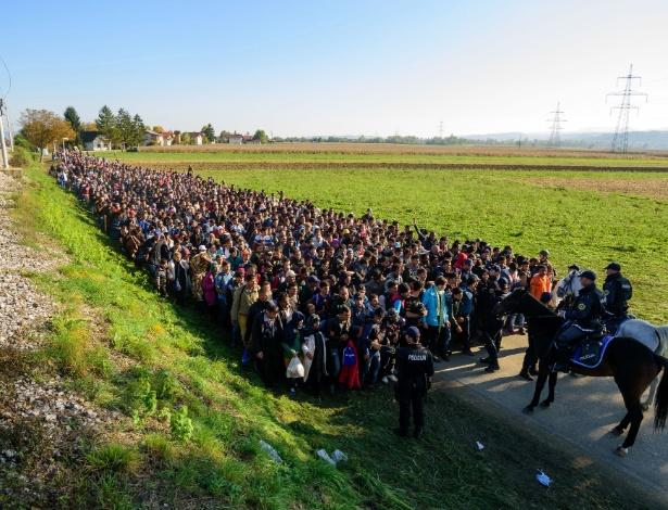 24.out.2015 - Policiais escoltam migrantes e requerentes de asilo até um centro de refugiados, após terem cruzado a fronteira croato-eslovena perto de Rigonce (Eslovênia)