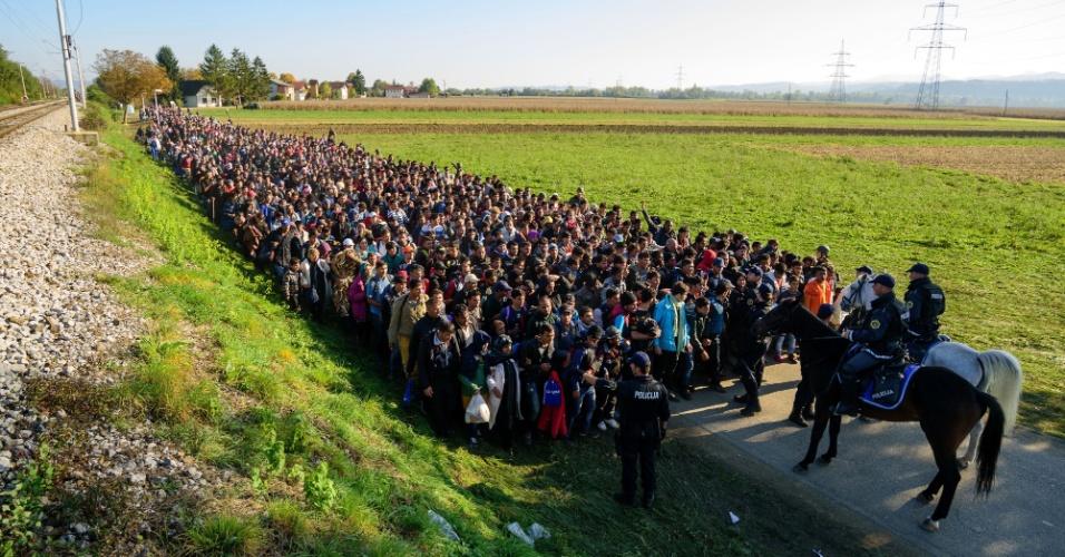24.out.2015 - Policiais escontam migrantes e requerentes de asilo que caminham para um centro de refugiados depois de cruzar a fronteira croato-eslovena perto Rigonce, na Eslovênia